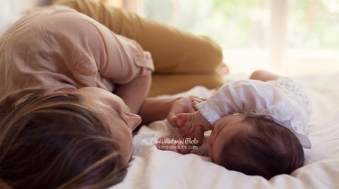 Madre y su bebé tumbados sobre la cama frente a frente