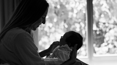 Contraluz de una mama cariñosamente sonriendo y acariciando la cara de su bebé colocado sobre sus rodillas