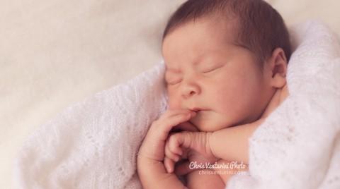 Recién nacido tumbado y envuelto en su arullo blanco con una mano en la boca