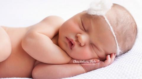 Primer plano de un recién nacido, con flor de lana en la cabeza, y tumbado de lado con la cabeza sobre las manos