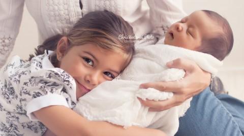 Niña abrazada a su madre y a su hermana recién nacidas