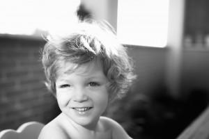 Retrato en blanco y negro de un niño con el sol en los ojos