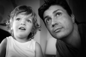 Retrato en Blanco y negro de un padre y su hijo pequeño contemplando el cielo desde la ventana de su casa