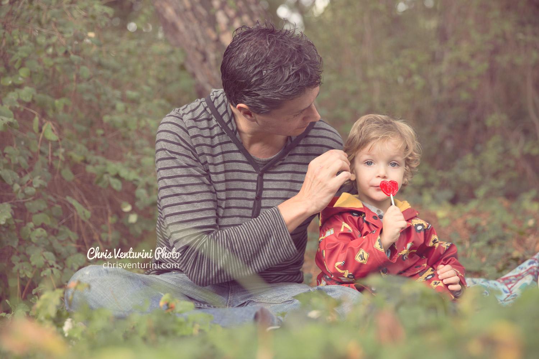 Niño sentado con su padre en el cesped de un parque en Madrid