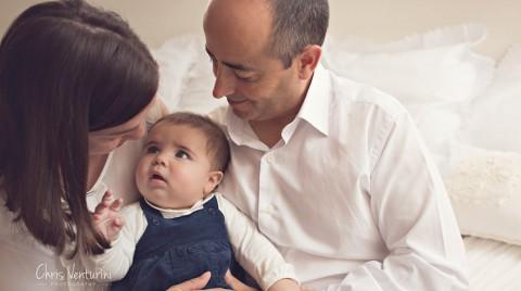 Bebé de 5 meses con sus padres en cama blanca