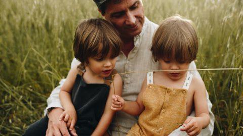 Padre sentado en un campo de hierbas altas, con dos niños pequeños sentados en sus piernas