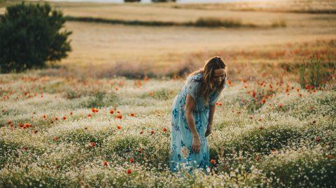 Mujer de pie, en un campo de amapolas con un vestido azul de flores, de espaldas al sol de atardecer.