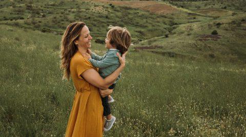Mujer con un vestido mostaza, y un niño en brazos, bailando en un campo de flores, en una tarde nublada.