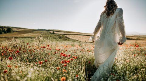 Mujer con un vestido blanco, a contraluz, en un campo de amapolas, de espaldas a la cámara.
